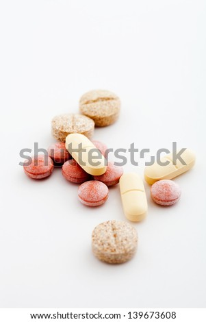 Bunch of colorful medicine pills on white background - stock photo