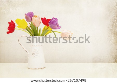Bunch of colorful tulip flowers in an old milk pitcher. Antique textured filter effect applied. - stock photo
