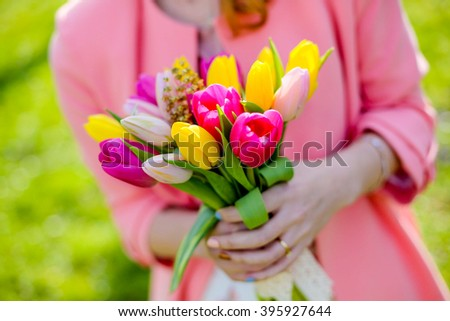 Bunch of colorful tulips in woman's hands, shallow dof.
