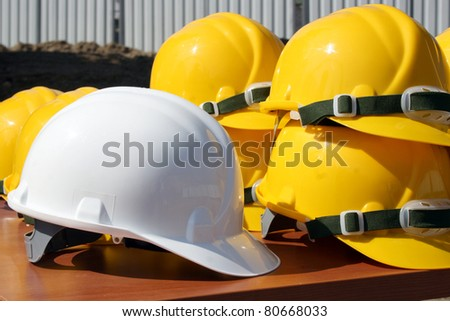 Bunch of construction helmets placed on wooden bench on construction site with one white wich is for head of staff