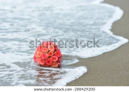 Bunch of crimson roses lying on sandy beach with surf closeup on water background, horizontal picture - stock photo