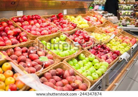 Bunch of different kind of apples on boxes in supermarket - stock photo