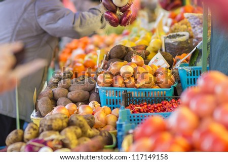Bunch of different onions, carrots, tomatoes and potatoes on city market