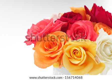bunch of different roses in a glass vase isolated on white