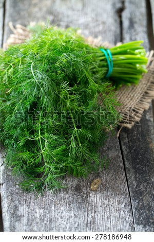 bunch of dill on wooden surface - stock photo