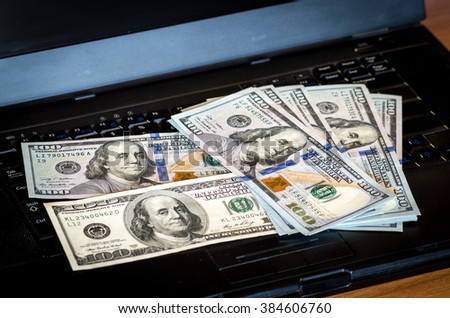 Bunch of dollar bill notes thrown on a laptop keyboard featured defocused bokeh - stock photo