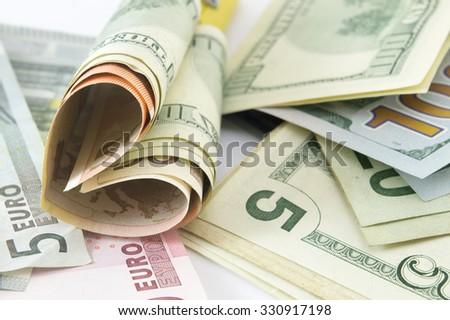 Bunch of dollar bills on the table forming a heart shape - stock photo