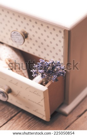 Bunch of dry lavender in decorative little shabby chic chest of drawers - stock photo