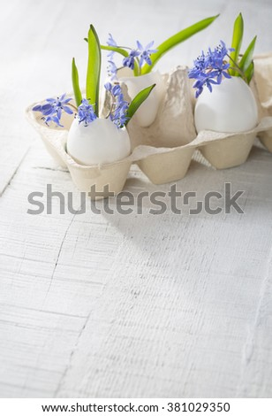 Bunch of early spring flowers ( Scilla siberica) in eggshells. Shallow depth of field, focus on near flowers. Easter decor - stock photo