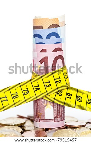 Bunch of Euro notes tied together with a tape measure on a pile of euro coins - stock photo
