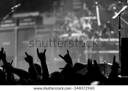 Bunch of fans happy during a concert throwing up the devil horns - stock photo
