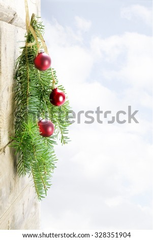 bunch of fir branches with red christmas baubles hanging as decoration on a rustic wooden wall, bright sky with clouds in the background, copy space - stock photo