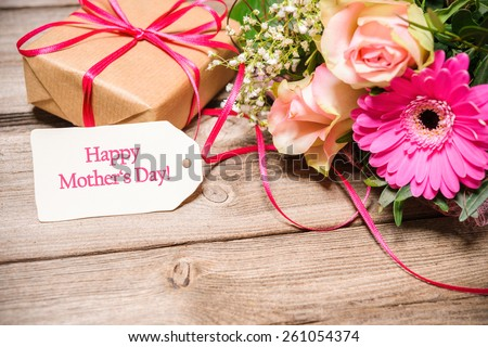 Bunch of flowers and tag with text on wooden background. Happy Mothers Day - stock photo