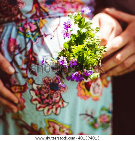 Bunch of flowers in the hands of pregnant in the sunny day