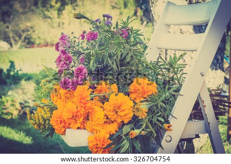 Bunch of flowers on a white chair on a blurry garden background, vintage photo.