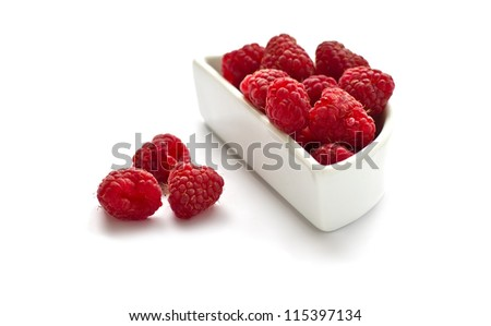 Bunch of fresh aromatic raspberries in white dish isolated on white background. Selective focus