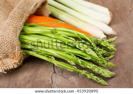 Bunch of fresh asparagus ,carrot,lemon grass, vegetables on wooden background