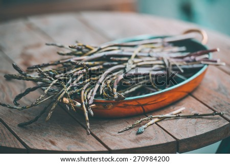 Bunch of fresh asparagus in copper dish on wooden table. Selected focus and shallow DOF. Toned picture - stock photo
