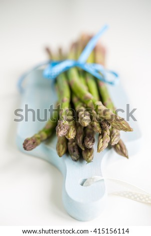 Bunch of fresh asparagus on a blue wooden cutting board with shallow depth of field - stock photo