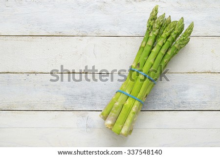 Bunch of fresh asparagus on a white wooden table. Empty copy space for editor's text. - stock photo