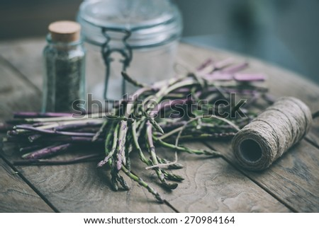 Bunch of fresh asparagus on wooden table. Selected focus and shallow DOF. Toned picture - stock photo