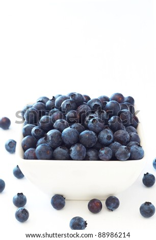 Bunch of fresh blueberries in ceramic bowl on white background