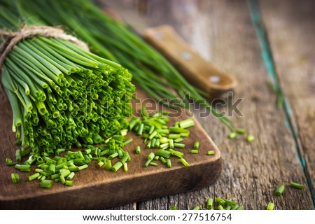 bunch of fresh chives on a wooden cutting board, selective focus - stock photo