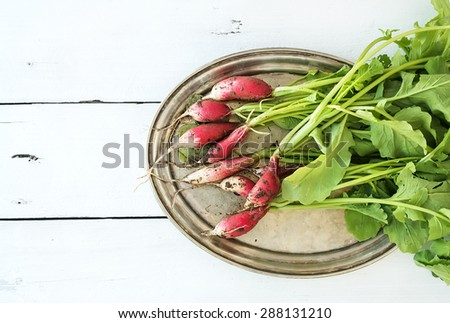 Bunch of fresh dirty garden radishes on vintage metal tray over rustic white wooden backdrop, top view, copy space - stock photo