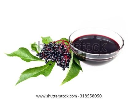 Bunch of fresh elderberry with green leaves and glass of elderberry juice - stock photo