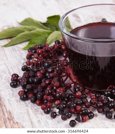 Bunch of fresh elderberry with green leaves and glass of elderberry juice on old rustic wooden background, healthy nutrition, alternative medicine and therapy - stock photo