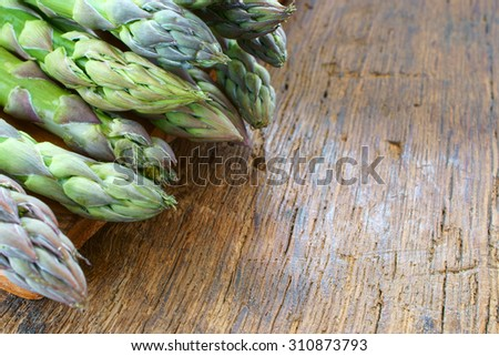 Bunch of fresh green asparagus spears on a rustic wooden table