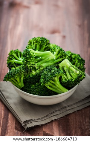 Bunch of fresh green broccoli on brown plate over wooden background - stock photo