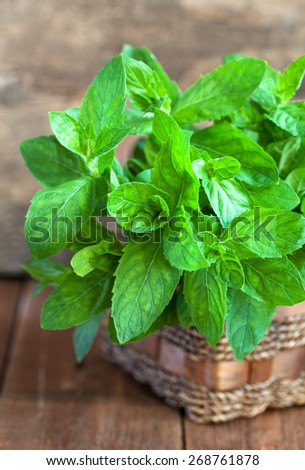 Bunch of fresh green mint in a basket on a wooden table, selective focus - stock photo