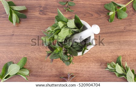 Bunch of fresh natural green mint in white glass mortar on wooden rustic board, healthy lifestyle and nutrition