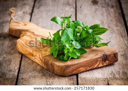 bunch of fresh organic basil in olive cutting board on rustic wooden background - stock photo
