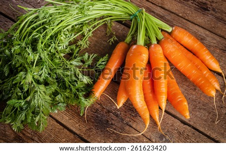 Bunch of fresh organic carrots. on grungy wooden background. - stock photo