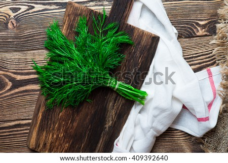 Bunch of fresh organic dill on a dark wooden cutting board - stock photo