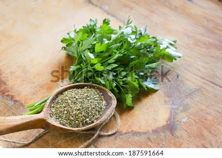 Bunch of fresh parsley and dry parsley in spoon  on wooden background. Selective focus. - stock photo