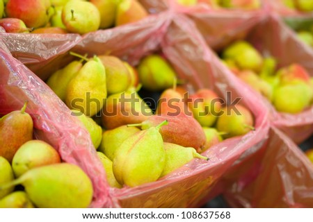 Bunch of fresh pears in boxes in supermarket