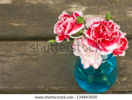 Bunch of fresh pink and white carnations in blue vase on wooden  background. Selective focus. - stock photo