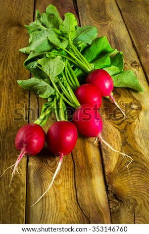 Bunch of fresh radish on a dark wooden background, selective focus, vertical/ Healthy eating, fresh ripe raw vegetables, diet vegetarian, vegan, macrobiotic food. Vegetables. Radishes   - stock photo
