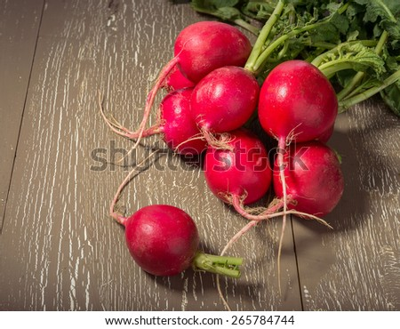Bunch of fresh radish on vintage wooden table - stock photo