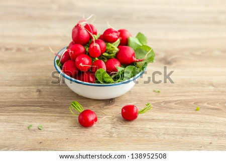 bunch of fresh radishes in a bowl with copy space - stock photo