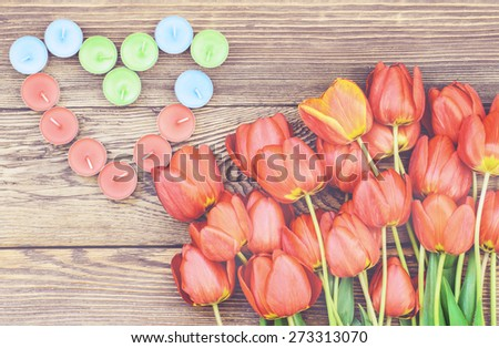 Bunch of fresh red tulips lying alongside a a heart formed of colorful candles for a loved one or sweetheart on Valentines Day or an anniversary, overhead view - stock photo