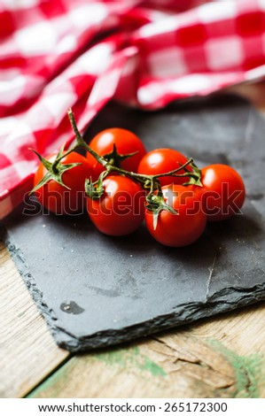 Bunch of fresh ripe red cherry tomatoes rich in antioxidants and vitamins on the vine on a dark grey kitchen counter with copyspace