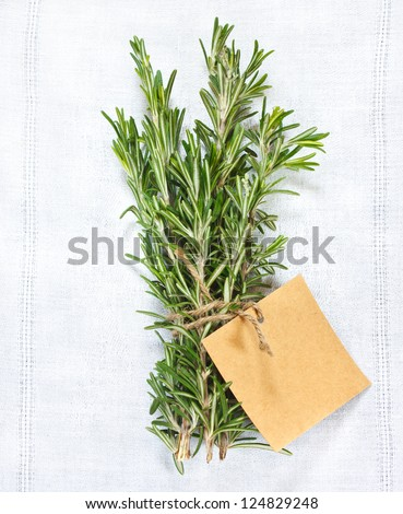 Bunch of fresh rosemary with tag on a white linen napkin. - stock photo