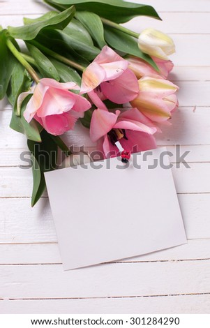 Bunch of fresh  spring  pink  tulips and empty tag  on white  painted wooden background. Selective focus. Place for text.
