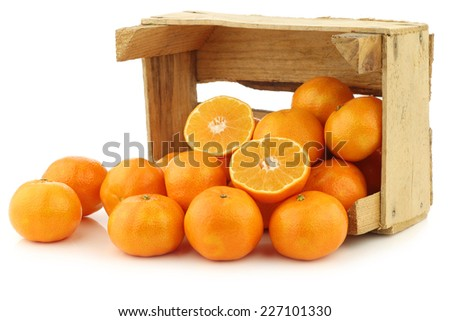 bunch of fresh tangerines and a cut one in a wooden box on a white background - stock photo