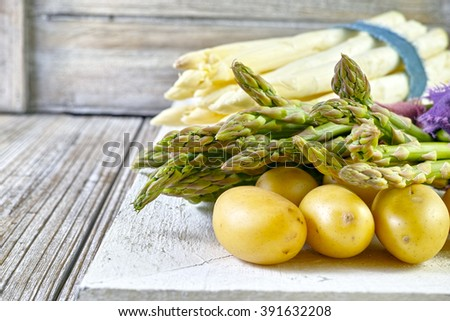 Bunch of fresh white and green asparagus and potatoes on wooden background, rustic style - stock photo