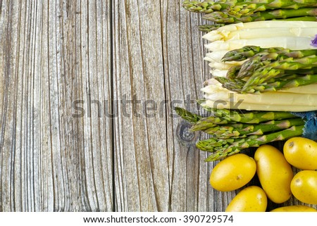 Bunch of fresh white and green asparagus and potatoes on wooden background, rustic style, copy space - stock photo